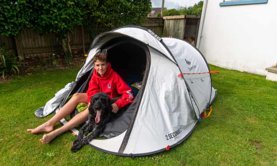 Max Woosey sits in his tent at home in Braunton, Devon, with Digby the labradoodle