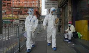 Government investigators wearing protective suits, walk in the Yau Ma Tei area, which is expected to be placed under lockdown, in Hong Kong on Friday.
