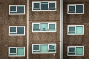 A woman looks out the window of her apartment at a North Melbourne public housing building. Several Melbourne public housing blocks were locked down due to a Covid outbreak.