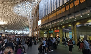 People wait inside Kings Cross station, where all train services were suspended for several hours.