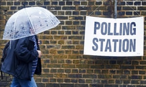 A man shelters from the rain as he arrives at a London polling station on EU referendum day, 23 June 2016.