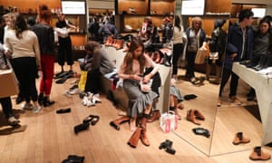 Customers try on shoes in Selfridges department store on Oxford street, London, during the Boxing Day sale