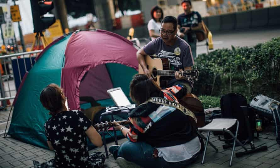protesters in Hong Kong at Admiralty district sit next to a tent playing guitars and singing