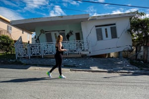A woman in Guanica passes a house damaged by the quake.