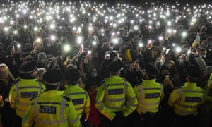 Police officers form a cordon as well-wishers turn on their phone torches as they gather at the bandstand on Clapham Common.