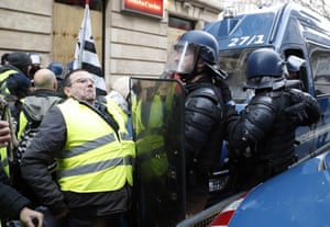 Riot police squeeze past a protestor