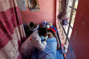 Secondary school student Jackline Bosibori, 17, who is pregnant, lies on a hospital bed as a midwife listens to her unborn baby's heartbeat at the Shofco health centre where she attends her antenatal clinic appointment.