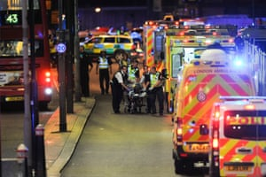 Police and ambulance officers help a victim injured in the attack on London Bridge.