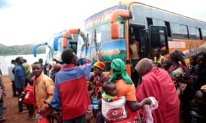 People disembark from a bus that transported them from Tanzania to neighbouring Burundi, as part of a repartition programme