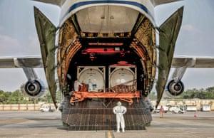 Ruslan plane crew members unload Linde tankers to help with coronavirus disease in Kolkata