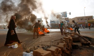 Protesters block a road with burning tyres and paving stones in Khartoum on Monday.