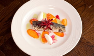 Soused mackerel with a dollop of sour cream, and discs of crunchy carrot on a round white plate