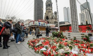People mourn at a makeshift memorial at the Kaiser Wilhelm Memorial church in central Berlin.