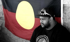 Boe Spearim with Aboriginal flag in the background