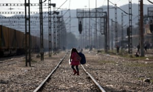 A child walks on a train track as migrants and refugees wait to cross the Greek-Macedonian borders