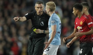 Manchester City's Oleksandr Zinchenko is booked by the referee for charging into Marcus Rashford.