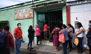 Parents wearing face masks queue to attend a ceremony marking the start of school at the Ramona Gil School in Chimaltenango, 60 km west of Guatemala City, on February 22, 2021.