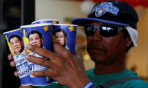 A supporter of Philippine presidential candidate Rodrigo Duterte holds cups he bought from convenience. The election is on May 9.