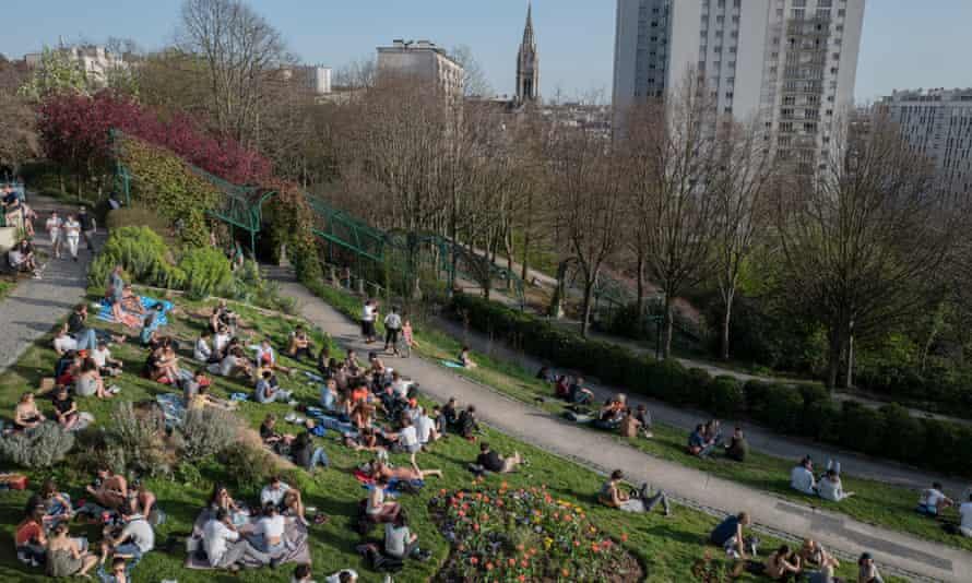 People enjoy the warm weather at Belleville park in Paris