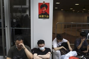 "Protesters below a photo of Hong Kong's chief executive Carrie Lam with the words ""Step down""."