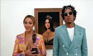 The Carters accept their award via video in front of a portrait of Meghan Markle.