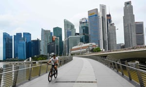 A man cycles along a bridge in Singapore on January 4, 2021, as the skyline is seen in the background.
