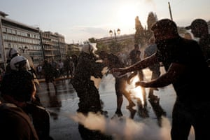 A police officer uses pepper spray against demonstrators during a protest against Covid vaccinations outside the parliament building in Athens, Greece.