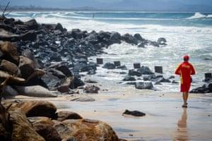 A lifeguard views beach erosion at Byron Bay Main Beach.
