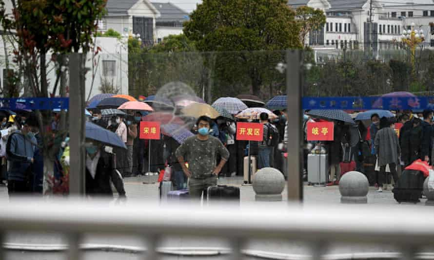 People wearing face masks to protect against coronavirus queue up outside to buy tickets at the railway station in Macheng, in China's central Hubei province.