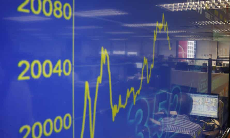 A TV screen showing a financial index rising