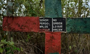 "A cross on the side of the road painted in the colours of the Nasa indigenous people, reads, ""Lord forgive them, fore they know not what they do."" Miranda, Cauca, Colombia"