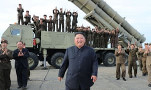 North Korea's official Korean central news Agency released this image of  Kim Jong-un celebrating the test-firing of a 'newly developed super-large multiple rocket launcher' at an undisclosed location on Saturday.