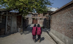 Iqra, left and her cousin Muskan walk back home after attending an ad-hoc learning centre set up in a local mosque as daily life is still paralysed by strikes and rolling curfews in Srinigar, Kashmir