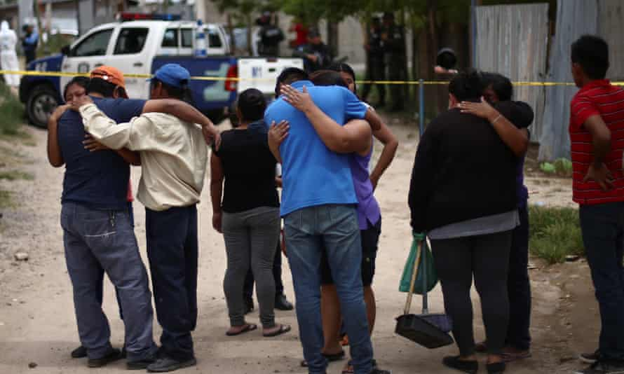 Relatives and friends react at a crime scene after a man was killed, in Tegucigalpa, Honduras. Violence in Central American countries is a major driver of migration.