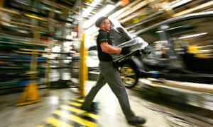 An employee prepares to fit a seat into a new Nissan Qashqai SUV automobile