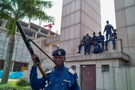 Policemen sit on a monument at the central station, Kinshasa.