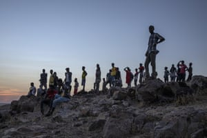 People who fled the conflict in Ethiopia's Tigray region stand on a hilltop overlooking Umm Rakouba refugee camp.