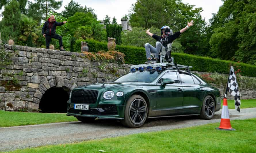 Andrew Flintoff rides on top of a Bentley while filming Top Gear