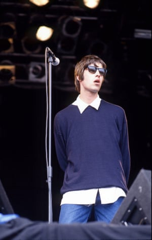 Liam Gallagher in 1994 nails the decade's style in his jumper, shirt and jeans. The feathered haircut and shades would likely have also been spotted in the crowd on Gallagher wannabes.