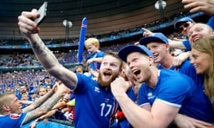 Iceland's Aron Gunnarsson celebrates with a fan after the team beat Austria.
