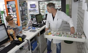 A Greek pharmacist serves a customer. Pharmacists have long been struggling with delays in reimbursements from the state, difficulties sourcing drugs and lack of funds.