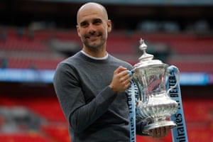 Manchester City manager Pep Guardiola holds the FA Cup trophy.
