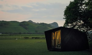 The Arthur's Cave cabin, seen at dusk and with its lights on. The cabin has panoramic views through its large sliding door. Inside the walls are wool-lined and there's a log fire. Design by Miller Kendrick Architects.