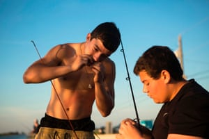 Howard Brunet and his cousin Reggie Parfait attach fishing bait to a rod, fishing being a traditional source of food and income