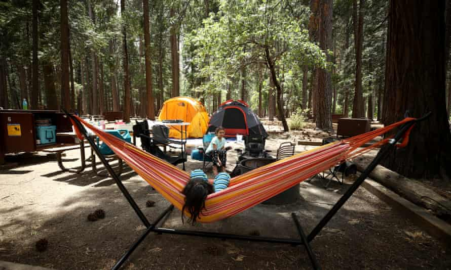 Noah (in hammock) and Valentina Gonzalez from the Sacramento area relax in their campsite in Yosemite national park, California.