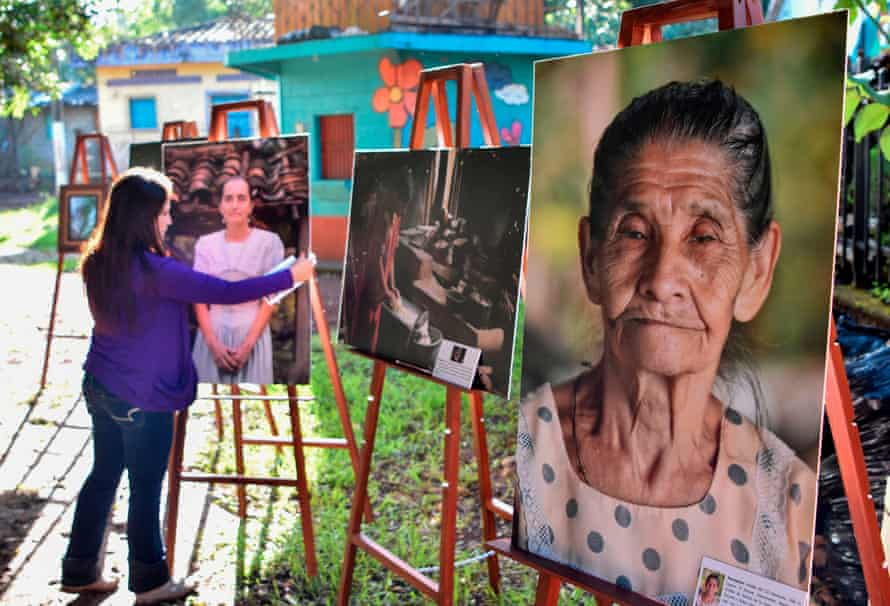 A woman places portraits of some of the survivors of the El Mozote massacre in a local park