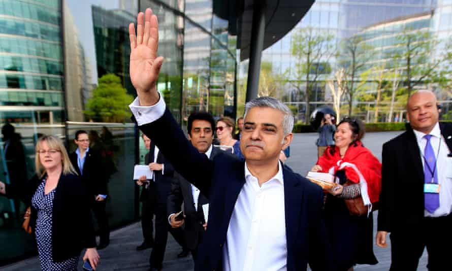 Sadiq Khan waves as he arrives at City Hall in London on his first day as mayor.