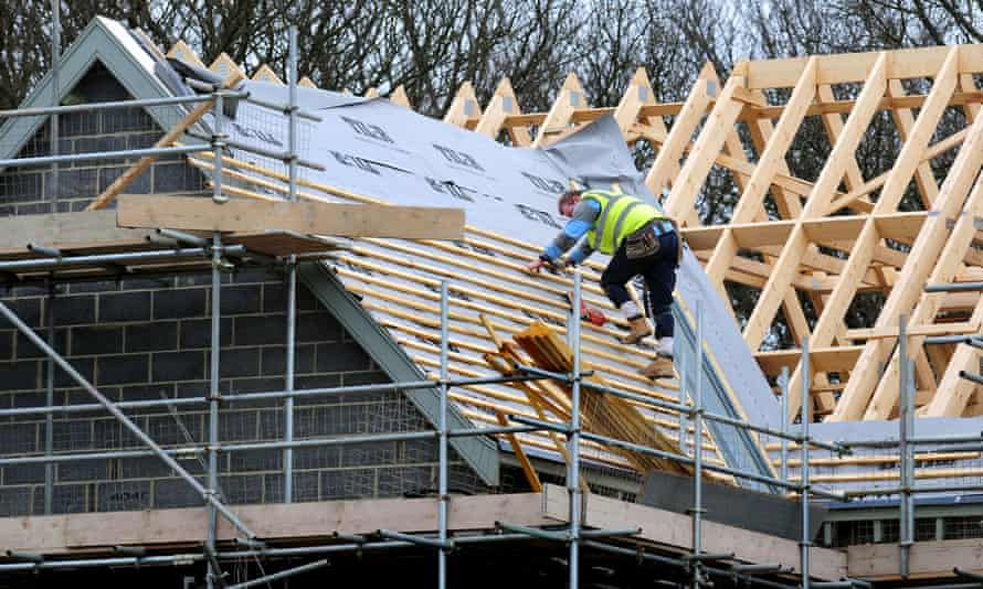 A construction worker on the roof of a house