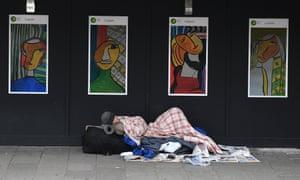 A homeless man sleeps near King's Cross in London