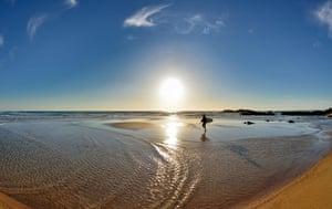Lonely surfer walking at scenic beach in Porto Covo, Portugal, Alentejo